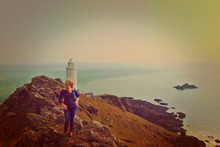 High Angle View Of Woman Standing On Cliff Against Lighthouse By Sea During Sunset