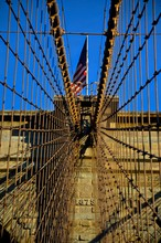 American Flag On Brooklyn Bridge Against Blue Sky