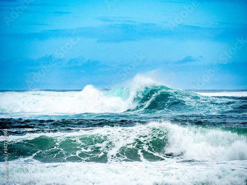 Big waves on the north shore of Oahu with aquamarine seas, white foam and blue skies Canvas Print
