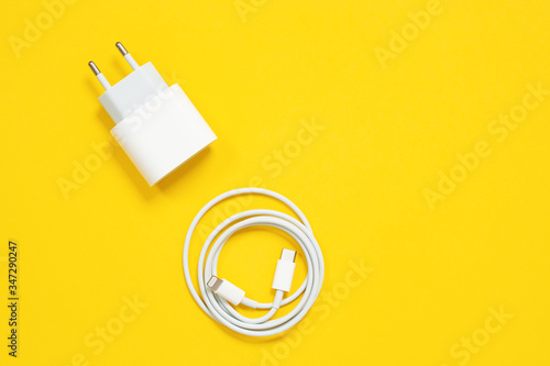 Fotografia Wrapped in a ring USB lightning cable and power adapter for charging smartphones and devices or for connecting gadgets to a computer or laptop on yellow background, top view, copy space