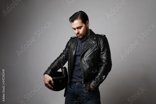 Vászonkép Vertical shot brutal bearded biker man wears helmet and dressed in a black leather jacket