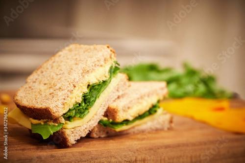 Cuadros en Lienzo Sandwich de rucula, queso y pasta de garbanzos, cortado a la mitad sobre una tab