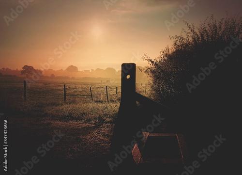 Fotografie, Obraz Built Structure Against Pasture At Sunset