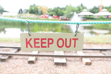 Close-up Of Keep Out Sign Hanging On Rope Against Railroad Track