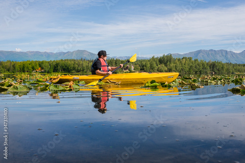 Teenager paddles a bright yellow canoe in a tranquil lily pad filled Alaskan lake Canvas Print