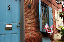 US Flags In The Window Of An Apartment Building On The Oldest Street Elfret's Alley In Philadelphia.