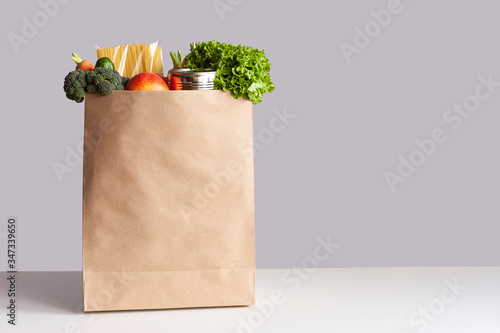 Papel de parede Various grocery items in paper bag on white table opposite gray wall