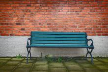 Empty Bench On Footpath Against Brick Wall