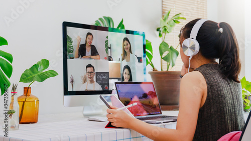 Fototapeta Asian business woman work from home with laptop, tablet and computer on table with meeting online and video conferencing.Concept of social distancing to stop the spread disease of Corona virus. obraz