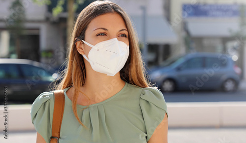 Fototapeta COVID-19 Pandemic Coronavirus Woman in city street wearing KN95 FFP2 mask protective for spreading of disease virus SARS-CoV-2. Girl with protective mask on face against Coronavirus Disease 2019. obraz