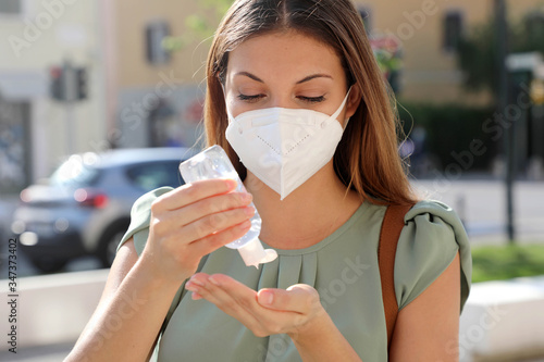Cuadros en Lienzo COVID-19 Pandemic Coronavirus Close up Woman with KN95 FFP2 Mask using Alcohol Gel Sanitizer Hands in City Street