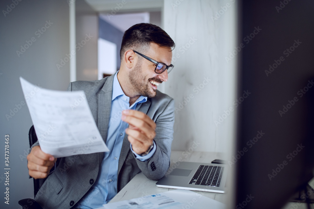 Fototapeta Attractive smiling unshaven caucasian businessman in suit and with eyeglasses holding paperwork and looking at laptop while sitting in his office.