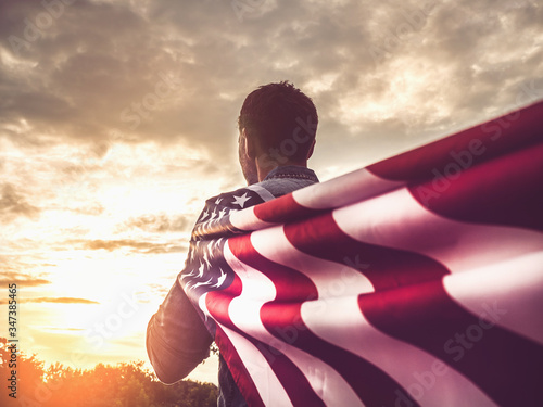 Attractive man holding Flag of the United States on blue sky background on a clear, sunny day Canvas Print