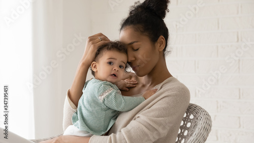 Foto Portrait of young african American mother hold hug little toddler baby relax tog