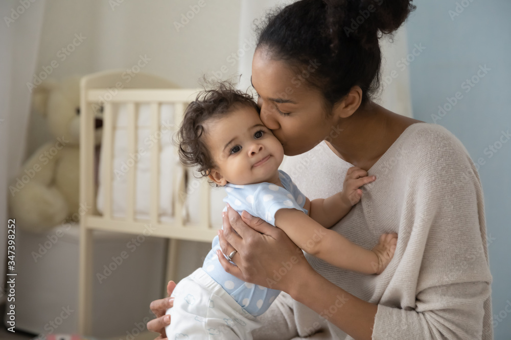 Fototapeta Loving young african American mother hold little newborn infant child kiss enjoying moment at home together, caring biracial mom embrace cuddle small baby toddler, maternity, childcare concept