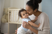 Loving Young African American Mother Hold Little Newborn Infant Child Kiss Enjoying Moment At Home Together, Caring Biracial Mom Embrace Cuddle Small Baby Toddler, Maternity, Childcare Concept