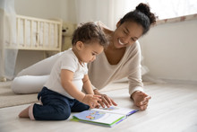 Smiling Young African American Mother Sit On Warm Floor Play With Little Infant Toddler Child, Happy Biracial Mom Relax Have Fun Read Book With Small Baby Girl At Home, Motherhood, Childcare Concept