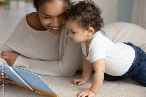 Happy young african American mom and little baby toddler relax at home bed readi Wallpaper Mural
