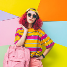 Fashionable Model With Pink Hair Poses With Backpack In Yellow Cap And Sunglasses. Summer Vacation Concept.