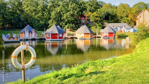 Foto Boathouses Reflection In River Against Trees