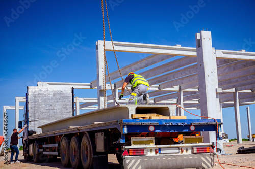 Worker is attaching crane hooks to concrete joist in truck trailer Canvas Print