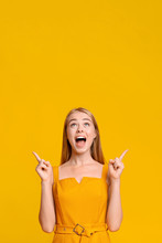 Look There. Excited Young Girl Pointing Fingers Upwards At Copy Space