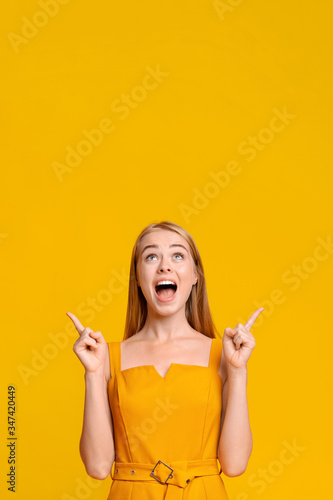 Look There. Excited Young Girl Pointing Fingers Upwards At Copy Space Fotomurales