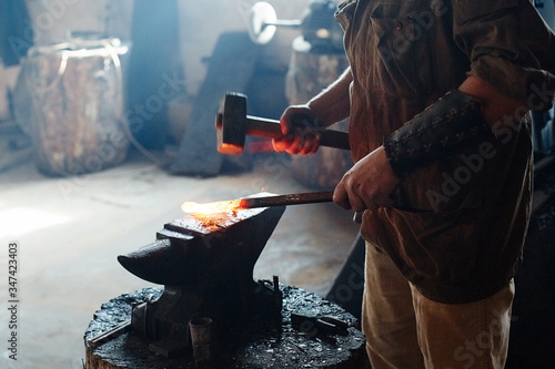 Photo Blacksmith working metal with hammer on the anvil in the forge