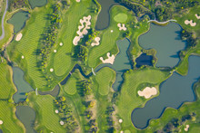 Aerial View Of A Golf Course Fairway And Green With Sand Traps, Trees And Golfers.
