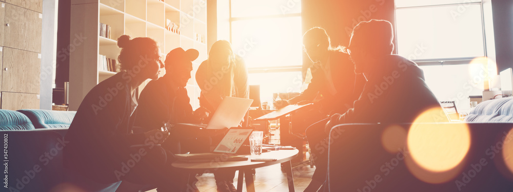 Fototapeta Silhouette of startup business team. Meeting on the couch. Big open space office. Five people. Intentional sun glare and lens flares. Wide screen, panoramic