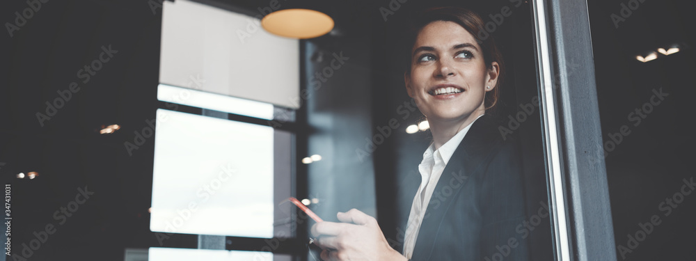 Fototapeta Portrait of charming business lady working in big open space office. Wide screen, panoramic