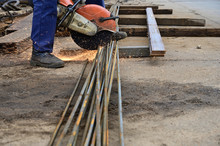 Photo Of A Worker Cutting Metal Reinforcement With A Circular Saw In The Open Air