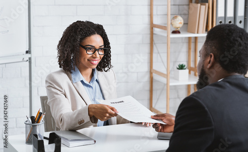 Fotografia HR manager interviewing young African American candidate in office