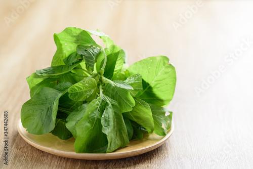 Green Thai spinach leaf or edible amaranth (Asian plant) on wooden plate, Organi Canvas Print