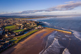 Aerial Photography of St Andrews at Sunset. From this photo both beaches of St Andrews can be seen, East Sands and West Sands as well as the iconic pier. Waves roll into the beaches on a wintry day.