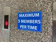 A sign warning message which has content is maximum five members per time is placed on a wall beside the elevator in an office during the pandemic of covid-19