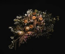 Closeup Shot Of A Luxurious Bouquet Of Orange And Brown Roses On A Black Background