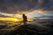 Beautiful young blonde woman in a bright bikini surfing in Mauritius on the background of incredible sunset with clouds and transparent waves