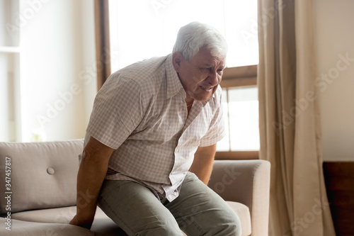 Photo Sick mature 80s man stand from couch suffer from sudden lower back muscle spasm