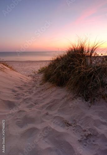 Fototapeta Wschód słońca na wybrzeżu Morz Bałtyckiego,wejście na plażę w Kołobrzegu,Polska. obraz
