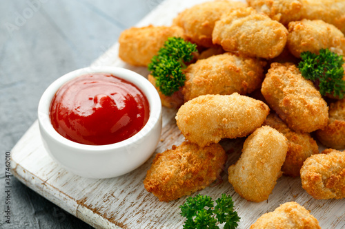 Fototapeta Crispy Battered scampi nuggets with ketchup on white wooden board obraz