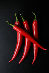 Fototapeta Przyprawy Four red chilli peppers with black background