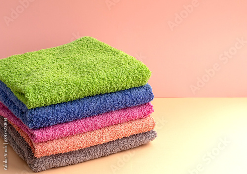 Valokuva terry towels of different colors lie exactly on a uniform background