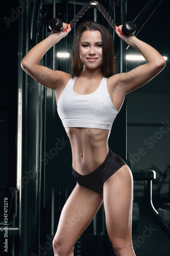 Fitness woman pumping up arm muscles in the gym Canvas-taulu