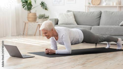 Fotografija Sporty senior woman doing yoga plank while watching tutorial on laptop