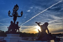 Low Angle View Of Sculptures On Bridge Railing Over River At Sunset