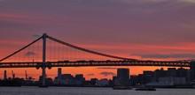 Rainbow Bridge Over Sea By City Against Sky During Sunset