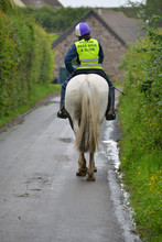 Horse Rider Moving Away From Camera Along Country Lane , The Rider Wearing Hi Viz Safety Gear To Keep Herself And The Horse Safe .