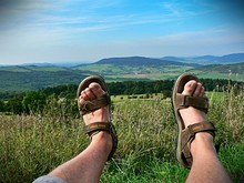 Low Section Of Man Wearing Sandals Against Landscape