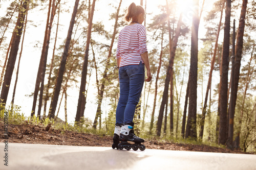 Photo Back view of female dresses casual attire rollerblading outdoors, spending her free time in forest, breathing fresh air, looking in distance, enjoying beautiful nature